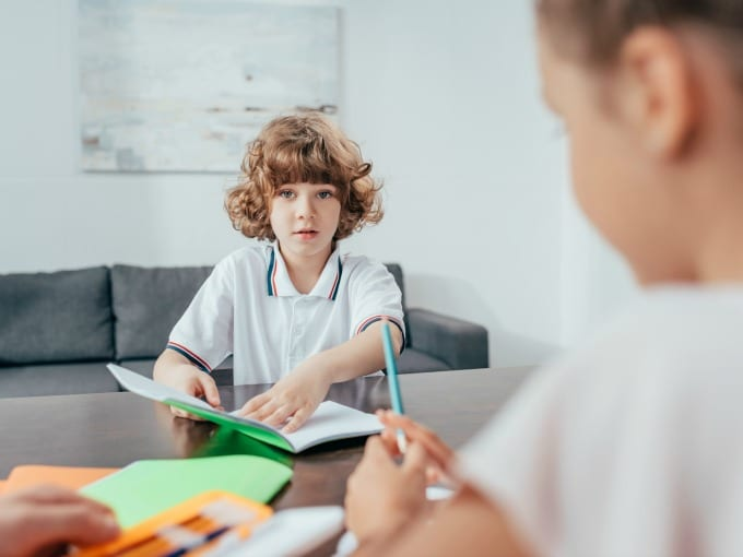 Young boy and girl sitting at a large table working on school projects.