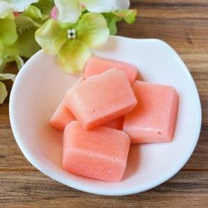 Square image of several sugar scrub bars in a small white bowl.