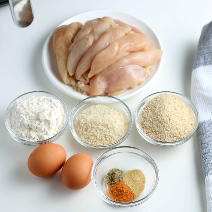 Ingredients for air fried chicken tenders - chicken, flour, breadcrumbs, eggs and seasonings.