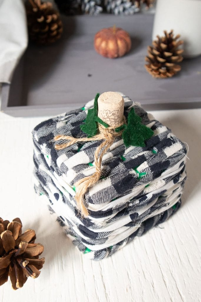 Black and white buffalo checked scrap fabric pumpkin, topped with a cork as the stem, with green felt leaves.