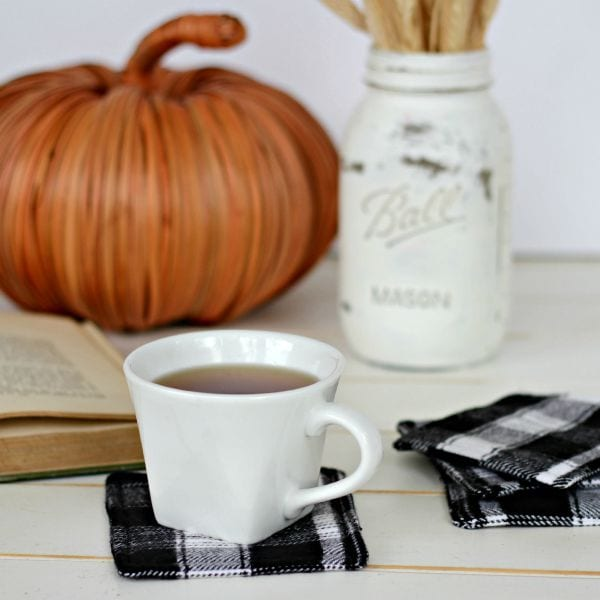 Image shows a coffee cup filled with coffee sitting atop a flannel homemade coaster. A mason jar, book, and pumpkin sit in the background.