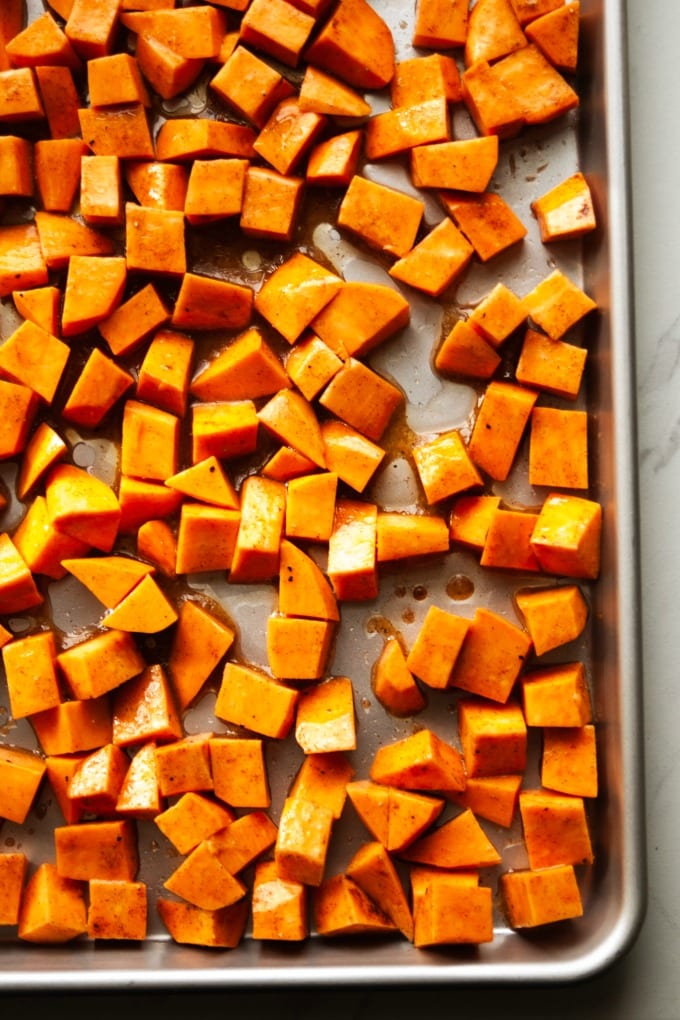 Raw sweet potatoes on a baking sheet.