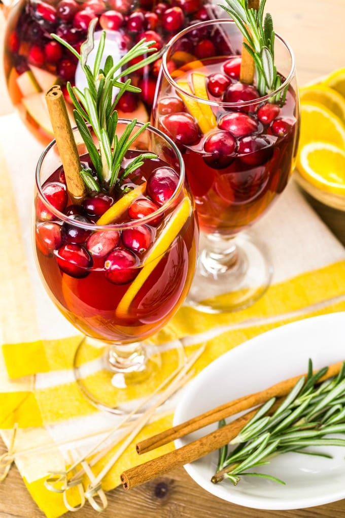 Cranberry Sangria with fresh cranberries, oranges, apples, pears and honey and garnished with a sprig of rosemary will really bring the holiday spirit to any gathering. With brandy and Cabernet Sauvignon, this sangria will have everyone cheering! via @jugglingactmama