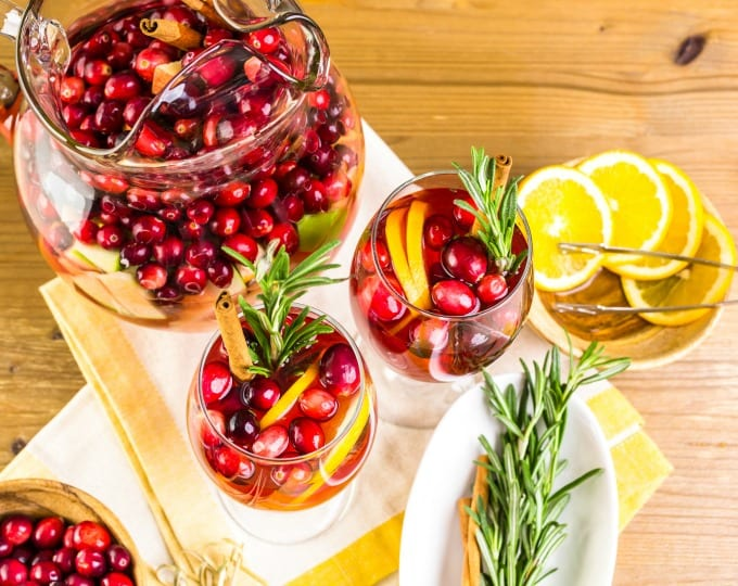 Top down view of a pitcher and two glasses of Cranberry Sangria with fresh cranberries, orange slices, chopped apples and pears. They are garnished with a sprig of rosemary and a cinnamon stick.