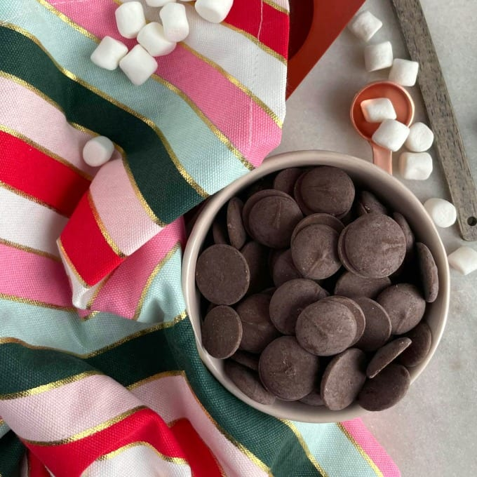 Melting chocolate wafers in a small ramekin surrounded by mini marshmallows and a cloth napkin.