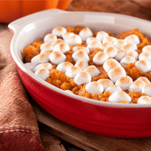 Sweet potato casserole topped with marshmallows in a red casserole dish