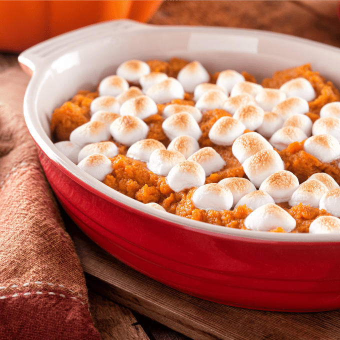 Make-ahead sweet potato casserole topped with marshmallows in a red casserole dish.