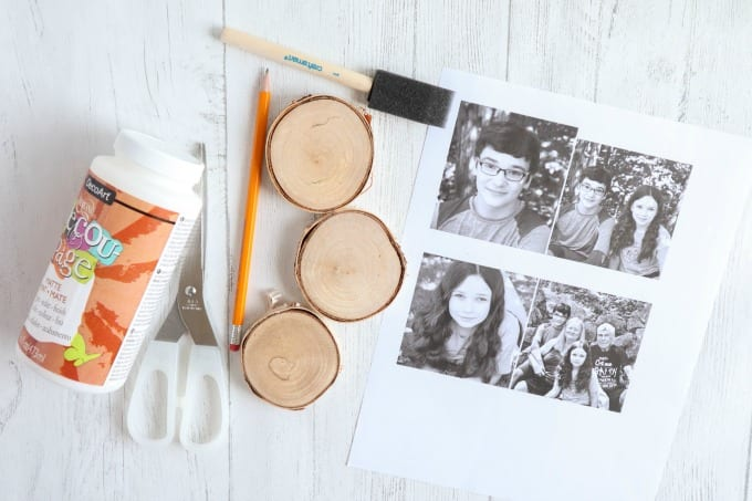 Materials needed to create wood photo ornaments, including wood slices, photographs, scissors, etc.