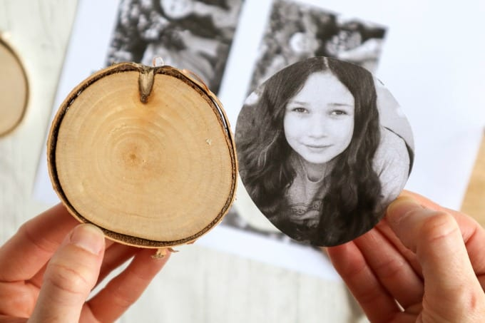 A hand holds a wood slice with a sized photo to be made into an ornament.