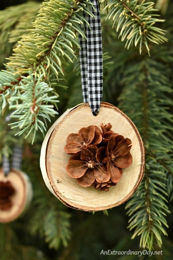 close up of wood slice ornament with rustic pine cone detail