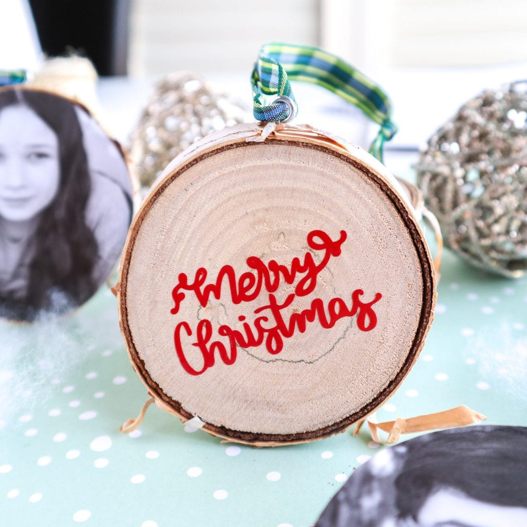 Close up of DIY wood slice Christmas ornament using vinyl for messages.