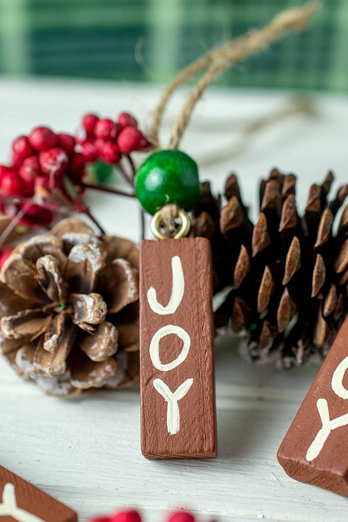 Painted Wooden Christmas Ornaments - this is a quick and easy DIY craft that's fun for the whole family. Our tutorial will show you how to make your own hand painted wood ornaments, plus we have ideas for personalizing these painted wood ornaments, too. #DIYcraft #ChristmasOrnaments #cheapcrafts via @jugglingactmama