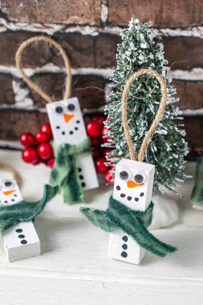 close up of Wooden Snowman Ornaments made of blocks pictured with bottle brush trees.