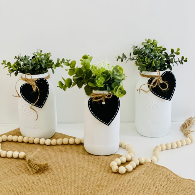Chalk Paint Mason Jars | Farmhouse Mason Jars - three chalk painted mason jar with Dollar Tree heart shaped tag decorated with twine and faux plants sitting atop burlap fabric.