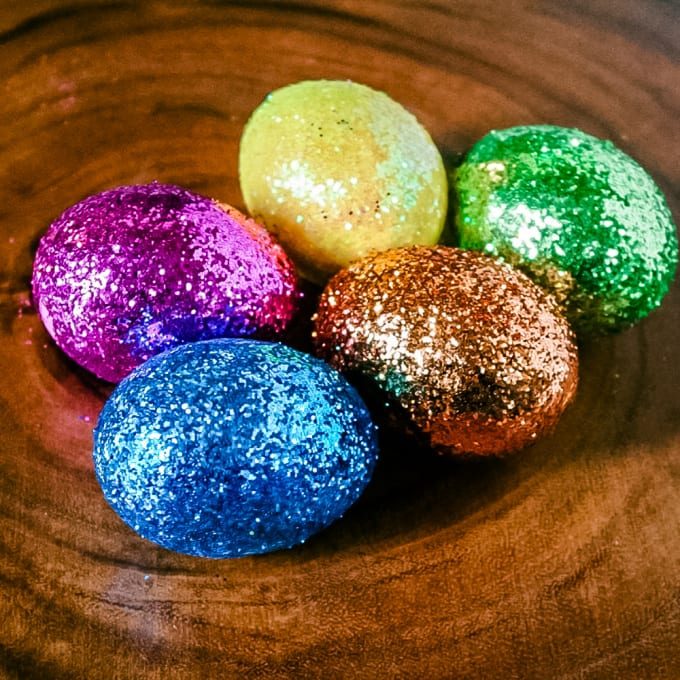 Glitter Easter Eggs on a wooden plate.