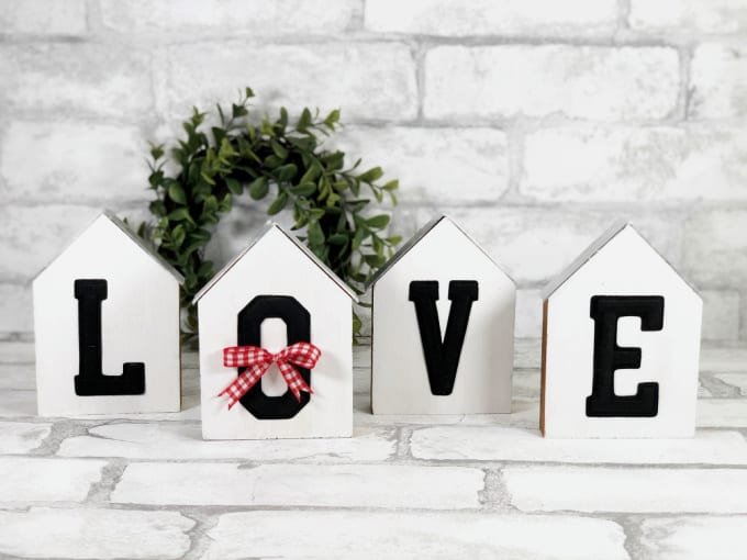 Decorative Wooden Houses | Wooden House Decor - four wooden blocks in the shape of houses with the letters L-O-V-E on them on a white brick background and a mall faux eucalyptus wreath in the background. The block with the letter O has a small red and white gingham wreath on it.