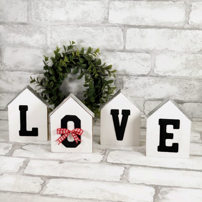 "Close up image of 4 farmhouse style mini houses decorated with the word ""Love""."