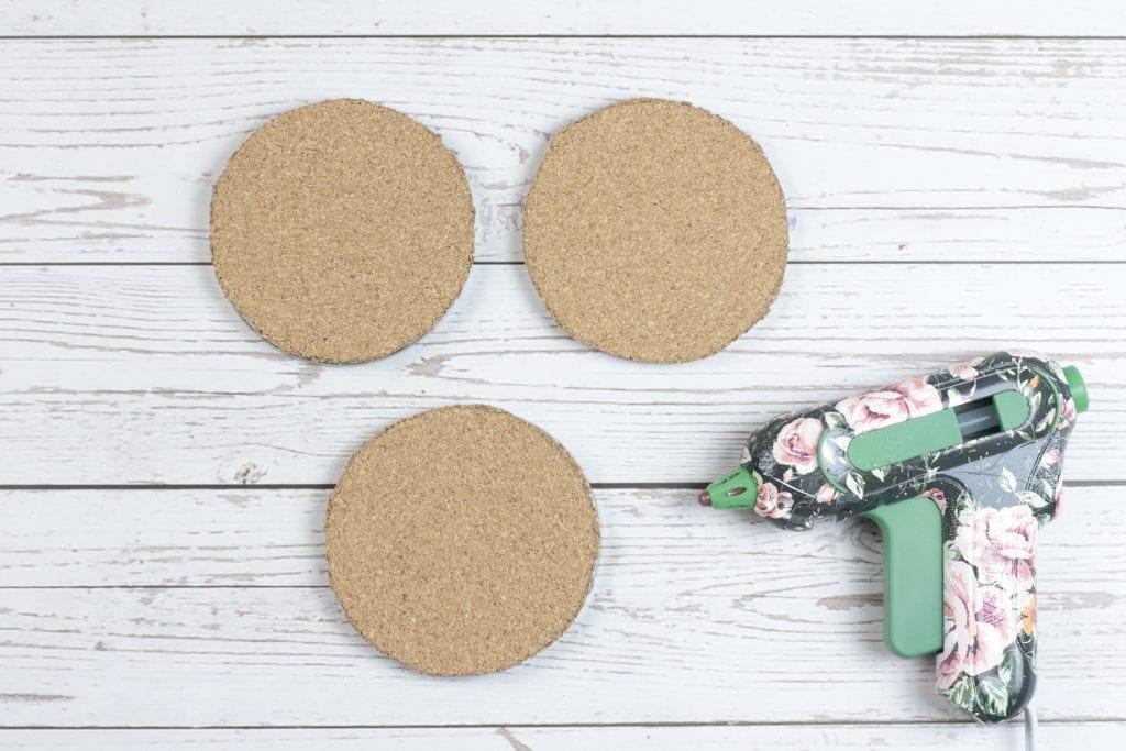 Mason Jar Lid Coasters DIY project: step by step instructions for making Mason Jar Lid Coasters with mason jar lids, a glue gun, paint, fabric, and cork.