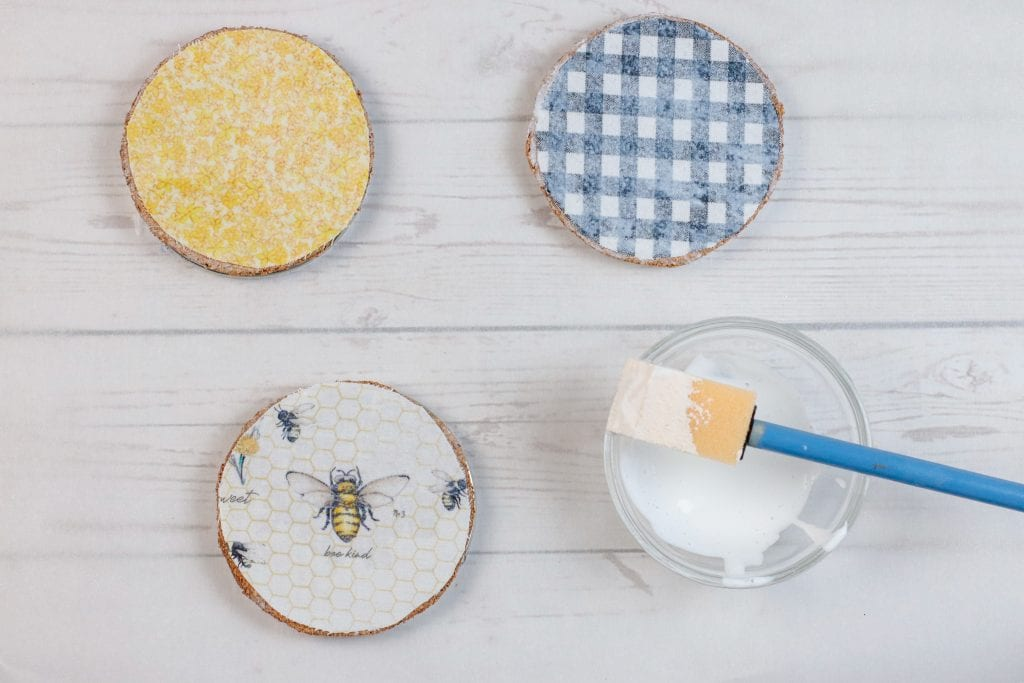 Mason Jar Lid Coasters DIY project: step by step instructions for making Mason Jar Lid Coasters with mason jar lids, mod podge, paint, fabric, and cork.