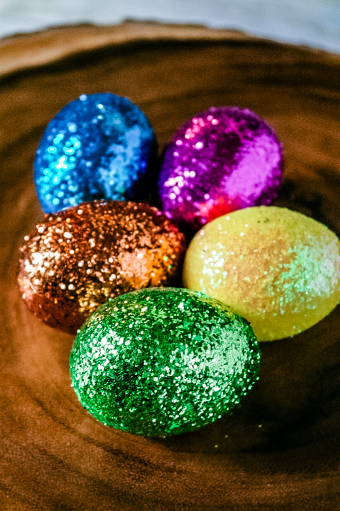 Close up image of hard-boiled eggs, painted in a variety of colors and covered in glitter. They sit on a wood surface.
