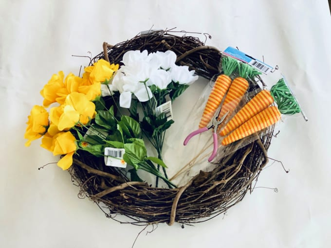 How to Make an Easter Wreath - all the materials needed to make a Grapevine Easter Wreath including a bare grapevine wreath, yellow and white silk flowers, wire cutters and faux craft carrots.