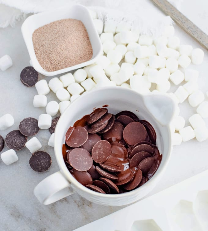 Image contains a small pitcher of melting chocolate wafers surrounded by marshmallows. Next to a small container of instant latte mix.