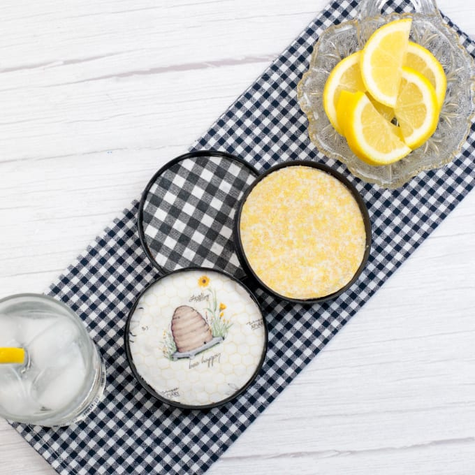 close up of Mason Jar Lid Coasters on a gingham checked towel with ice water and lemons