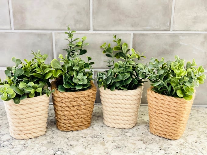 Mini DIY Dollar Tree Planter - close up of four mini plastic containers wrapped with cotton rope and jute rope. Faux eucalyptus is in each of the pots, which are eon a granite counter top with gray tile in the background