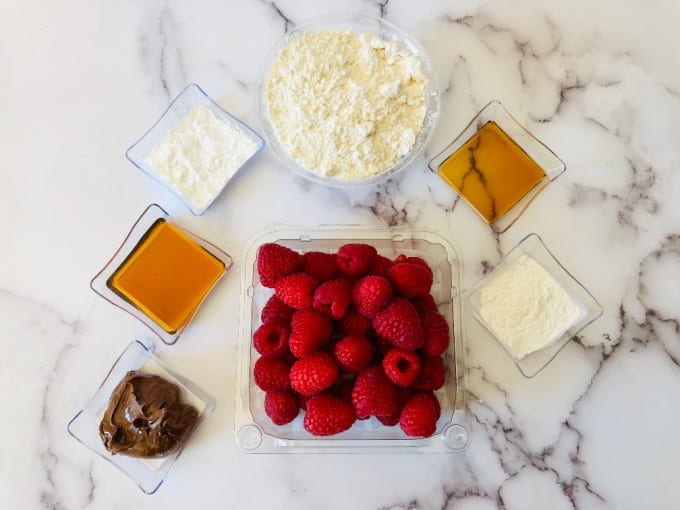 close up of Bundt Cake Breakfast Recipe ingredients in small bowls including raspberries and maple syrup.
