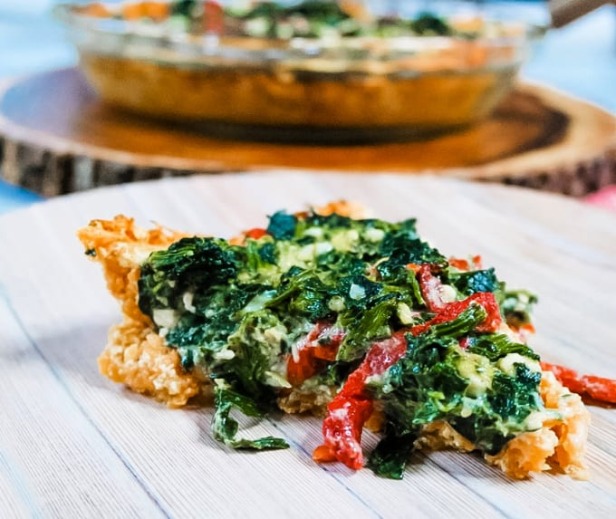 Slice of spinach and sweet potato quiche on a wood platter.