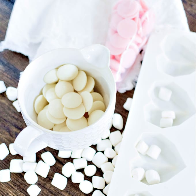 White chocolate melting wafers in a ceramic measuring cup surrounded by mini marshmallows. It sits next to a silicone mold.
