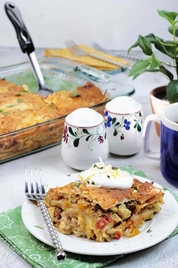 A slice of breakfast enchilada casserole on a white plate with a fork. They sit on a green cloth napkin.