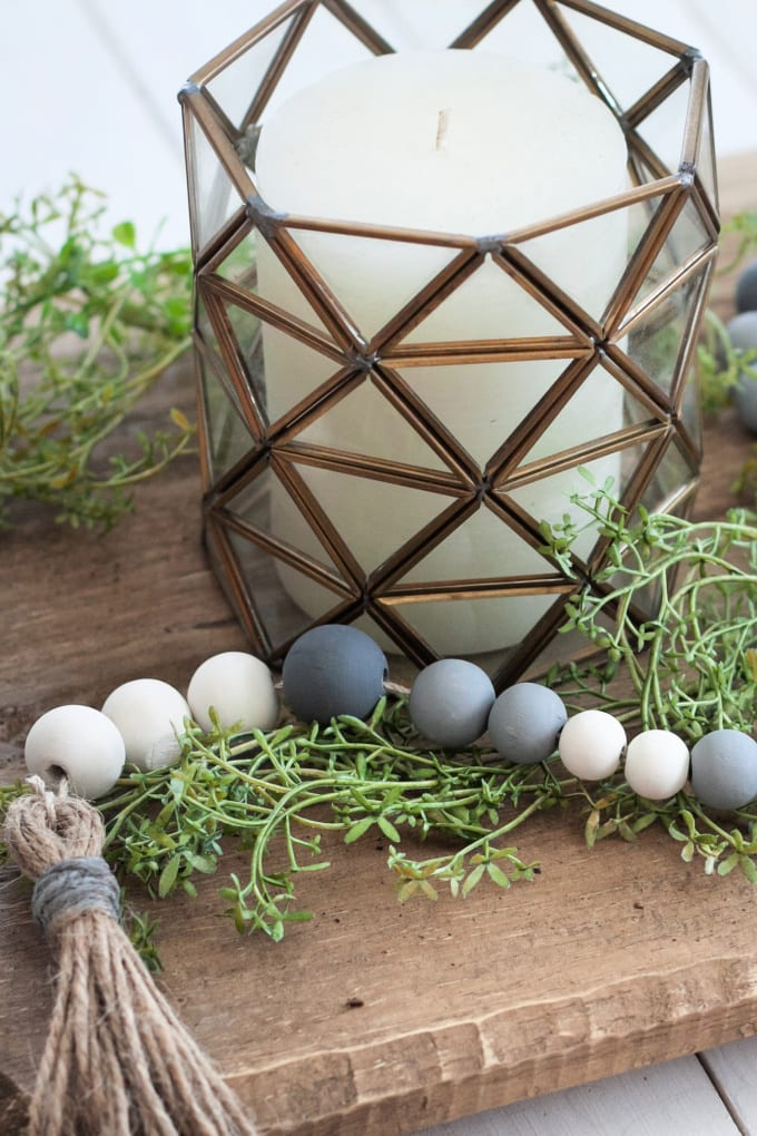 Close up image of a gray and white wooden bead garland on top of a wood plank. It is surrounded by a glass candle holder.
