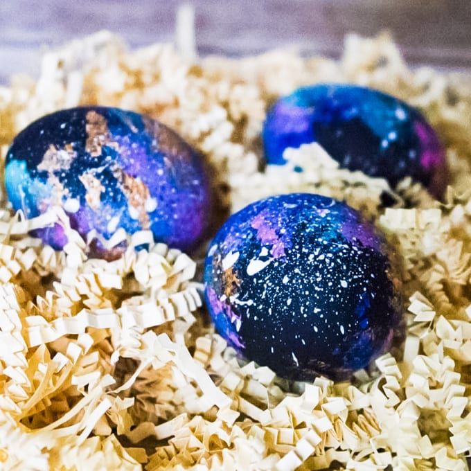 Close up of DIY Galaxy Eggs painted with black, blue, teal, pink and gold and flecked with white.