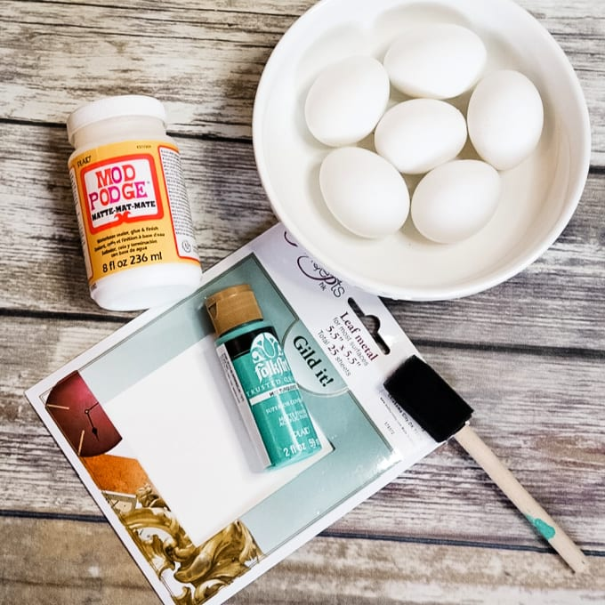 close up of materials needed to make DIY Gold Leaf Easter Eggs including golf leaf, acrylic paint, and Mod Podge.
