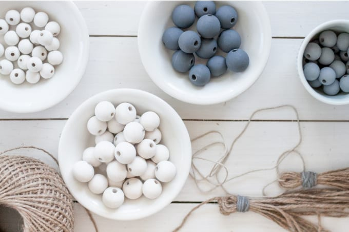 Top down view of gray and white wooden beads in small white bowls.