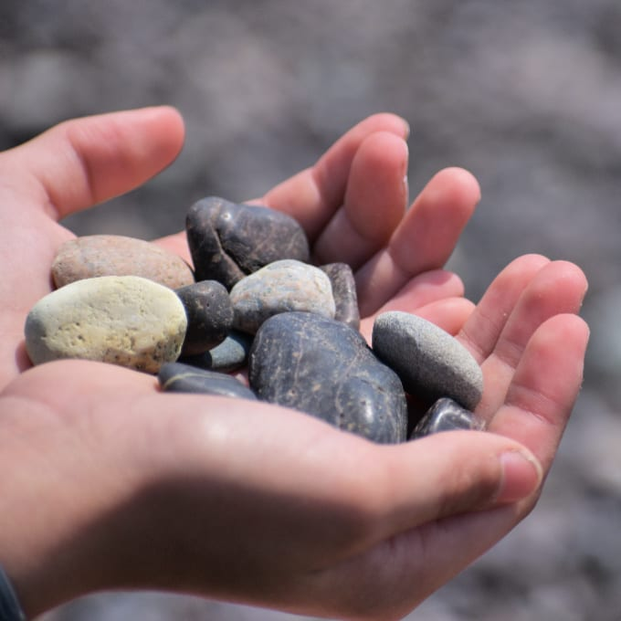 Hands holding smooth stones found on a beach