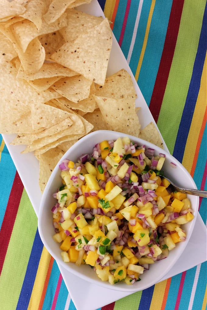 Pineapple Mango Salsa Recipe - with fresh pineapple, mango, red onion and jalapeno seasoned with lime juice and just a pinch of salt, this is one tasty salsa that you're going to want to put on just about everything! via @jugglingactmama