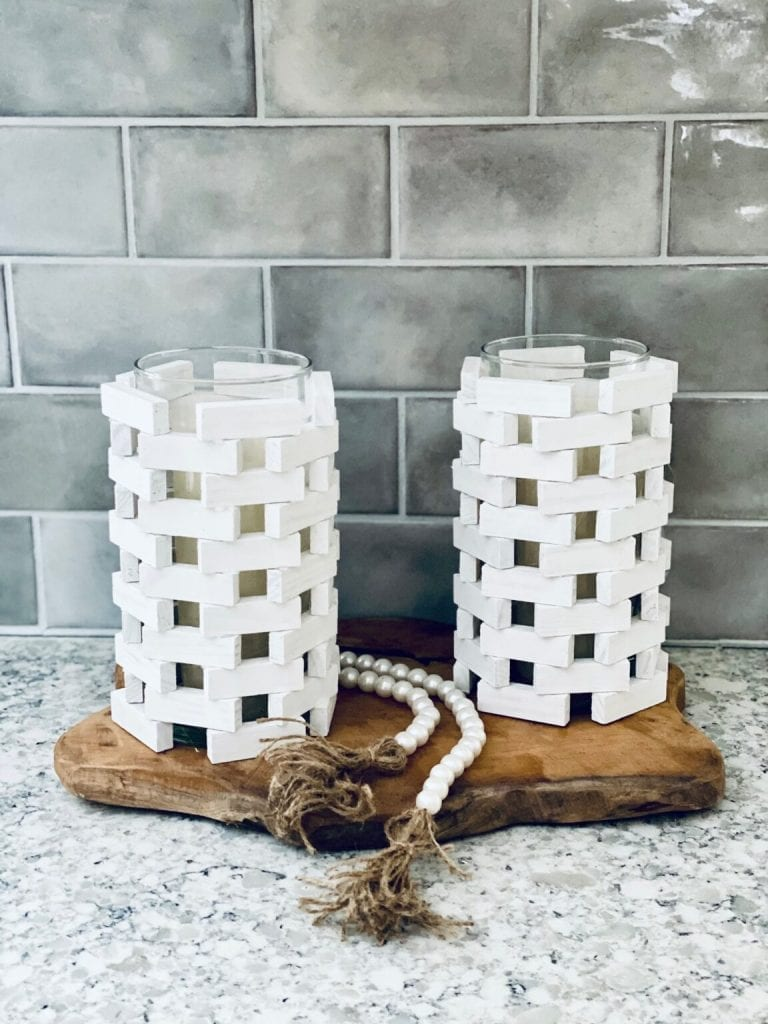Close up image of candle holders made from old Jenga pieces atop a wood slice