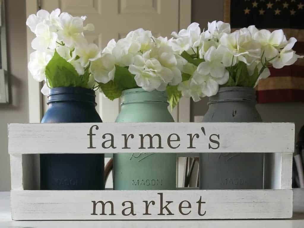 Wooden crate filled with painted mason jars to create a farmhouse crate centerpiece