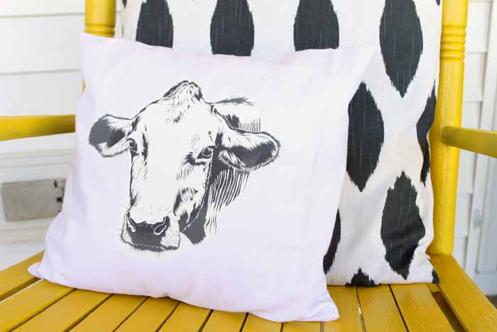 Close up image of two farmhouse style decor pillows on a yellow rocking chair. One has a cow head printed on it, the other is an Ikat pattern