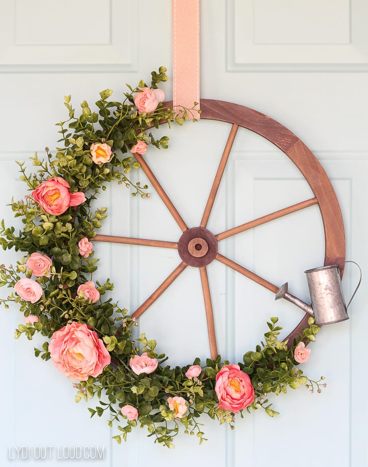 DIY Farmhouse style wreath made from an old wagon wheel and accented with pink flowers