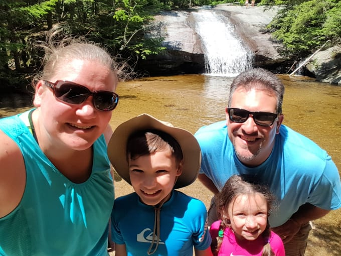family of four at Beede Falls Sandwich NH with the waterfall in the background.