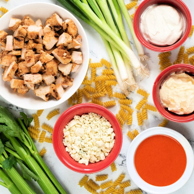 Ingredients needed to make Buffalo Chicken Pasta Salad including celery, blue cheese crumbles, buffalo sauce, mayonnaise, sour cream, and chicken.