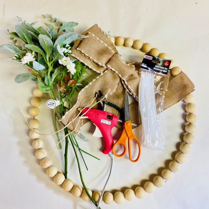 Materials to make a farmhouse wooden bead wreath - image contains a wood bead wreath, bow, greenery, hot glue gun and scissors.