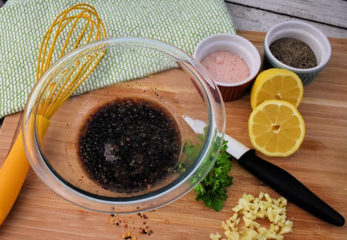 Ingredients to make an easy steak marinade - image includes a large glass mixing bowl filled with liquid, surrounded by a whisk, seasonings and lemon slices.