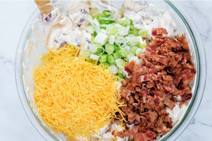 Glass bowl filled with the ingredients for loaded potato salad