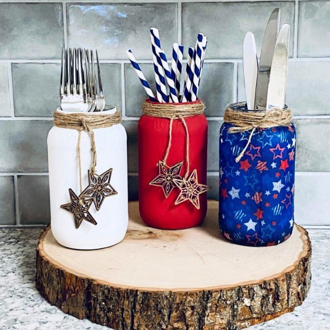 Learn how to paint mason jars in this tutorial. Image contains 3 painted and decorated mason jars sitting on top of a slice of wood.