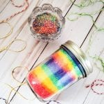 Rainbow bath salts in a glass mason jar next to a small bowl filled with the same.