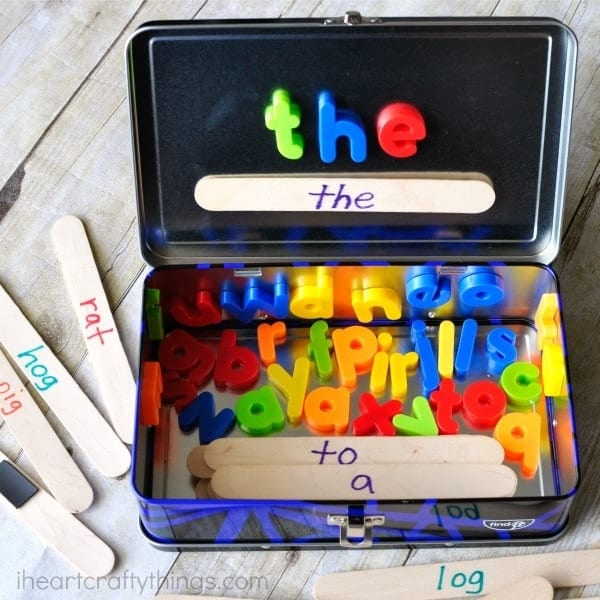 Metal lunchbox with magnetic letters and popsicle sticks create a word building activity travel kit